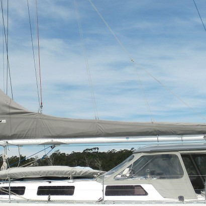 Grey mainsail cover, deck spray dodger with pvc windows